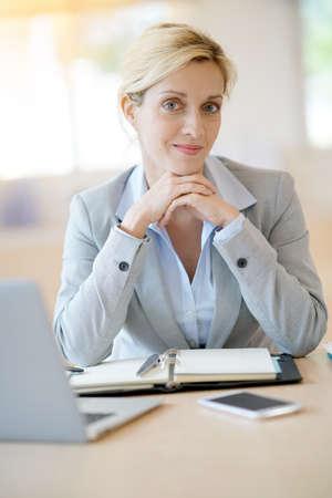 Businesswoman working in office on agenda Stock Photo