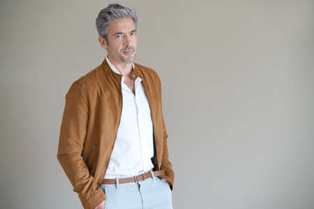 mature man: Mature man standing on grey background, isolated Stock Photo