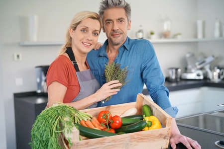 meat lover: Portrait of couple in domestic kitchen holding basket of fresh vegetables