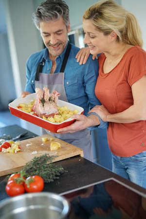 meat lover: Middle-aged couple having fun cooking together in home kitchen