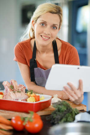 domestic kitchen: Woman in domestic kitchen reading cooking receipe on tablet