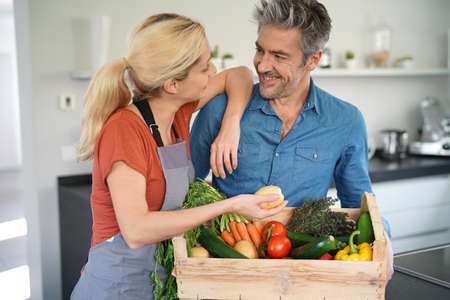 complicity: Portrait of couple in domestic kitchen holding basket of fresh vegetables