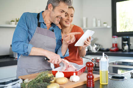 electronic tablet: Couple in home kitchen using electronic tablet
