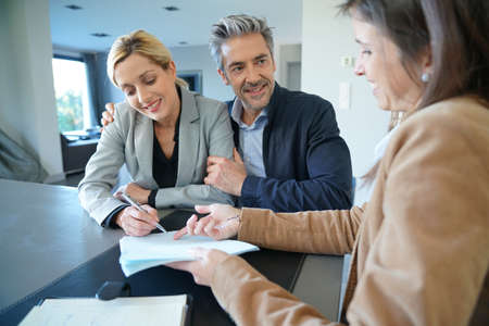 salesgirl: Clients signing sales agreement with real-estate agent Stock Photo