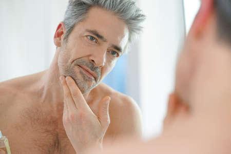 Portrait of mature man in front of mirror applying facial cream Stock Photo