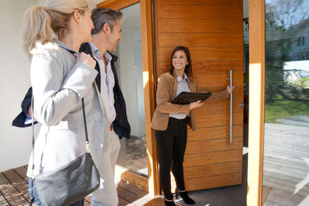 Real estate agent inviting couple to enter house for visit Stockfoto