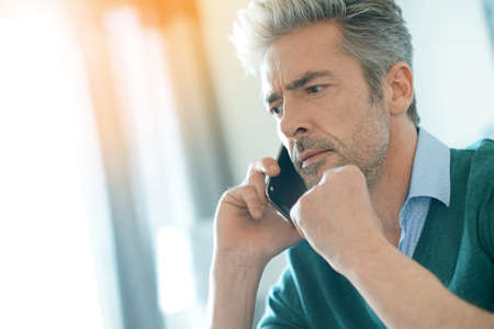 Middle-aged man at home talking on phone Imagens