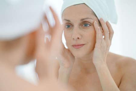 portret van een vrouw in de badkamer die hydraterende crème toepast Stockfoto