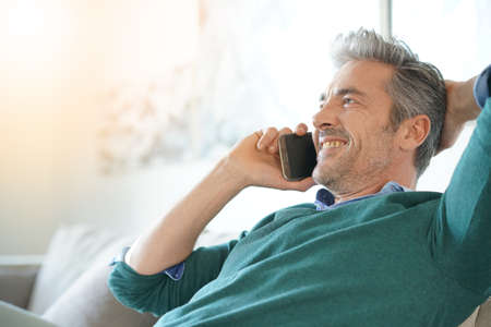 Middle-aged man at home talking on phone Stock Photo