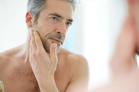 beautycare: Portrait of mature man in front of mirror applying facial cream Stock Photo