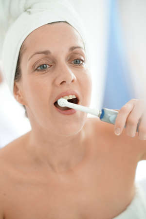 Woman in bathroom brushing her teeth with electronic toothbrush