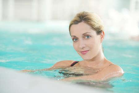 Femme blonde de détente dans la piscine spa