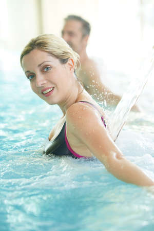 Woman enjoying water jet in thermal bath Banque d'images