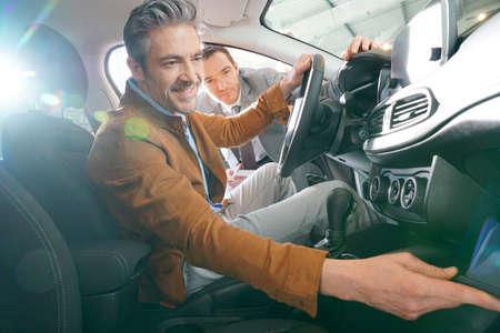 Man sitzt im Fahrzeug in Autohaus