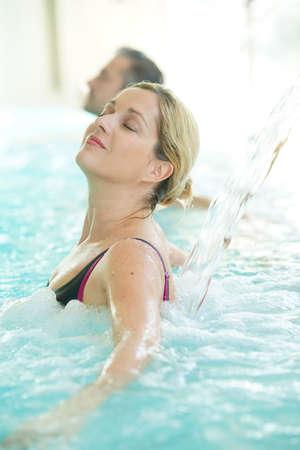 Femme appréciant jet d'eau dans le bain thermique Banque d'images