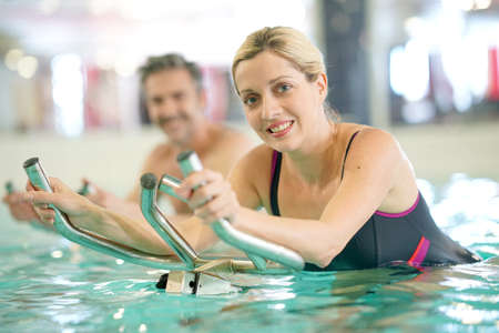 Couple in swimming-pool doing aquabike exercises Stock Photo