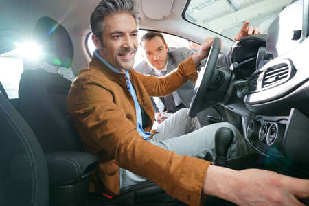 Man sitzt im Fahrzeug in Autohaus Standard-Bild