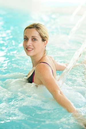 Femme dans une piscine thermale en profitant jet d'eau