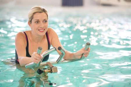 Vrouw in zwembad doet aquabike oefeningen