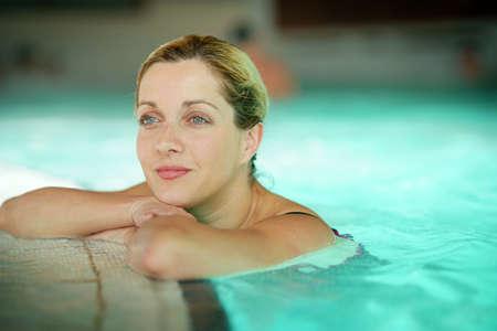 Femme blonde de détente dans la piscine spa Banque d'images