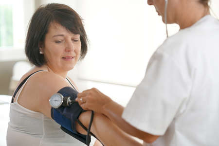 medicalcare: Mature woman at the doctor, controlling blood pressure