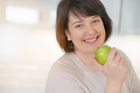 donne obese: Cheerful mature woman eating green apple