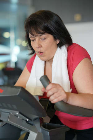 eliptica: Overweight woman at the gym doing cardio exercises on bike