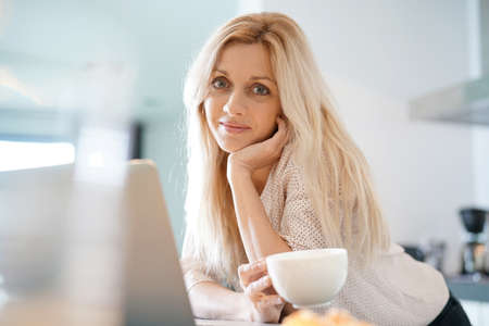 woman smiling: Beautiful blond woman at home connected on laptop Stock Photo