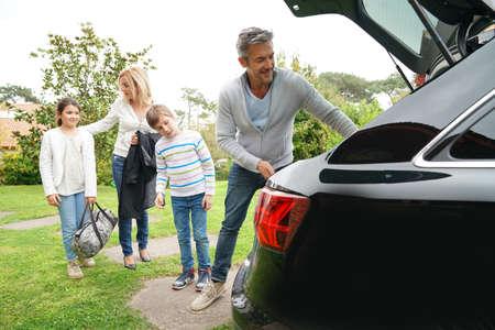 tronco: Familia de cuatro cargando el tronco del coche para irse de vacaciones