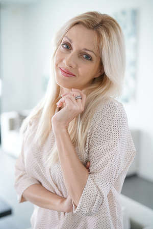 Portrait of beautiful blond woman standing at home Stock Photo