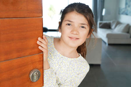 Portrait of young girl opening front door of the house