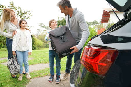 car trunk: Family of four loading car trunk to leave for vacation