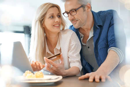 Middle-aged couple at home shopping on internet Stock Photo