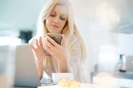 homeoffice: Blond woman with eyeglasses connected on smartphone at home Stock Photo