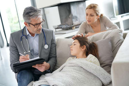 medicalcare: Doctor visiting sick little girl at her house Stock Photo