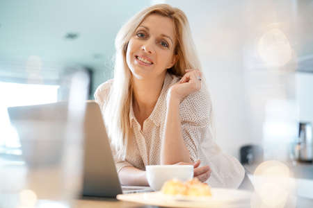 homeoffice: Beautiful blond woman at home connected on laptop Stock Photo
