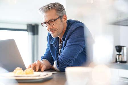 ハンサムな 45 歳男性自宅のラップトップに接続されています。
