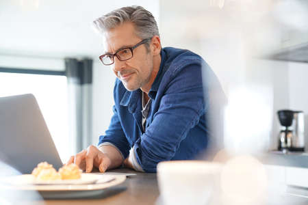 Handsome 45-year-old man at home connected on laptop