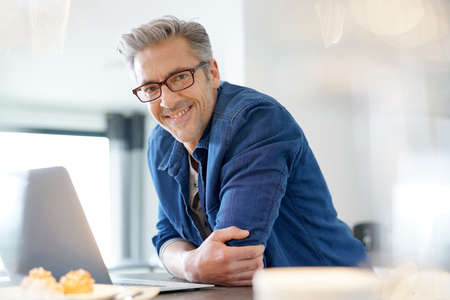 homeoffice: Handsome 45-year-old man at home connected on laptop