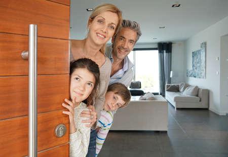 Familie von vier öffnenden Haustür Standard-Bild