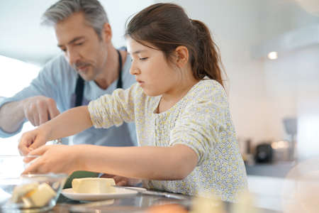 complicity: Daddy with daughter baking cake together in home kitchen