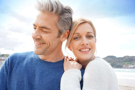 adult couple: Middle-aged couple embracing each other at the beach