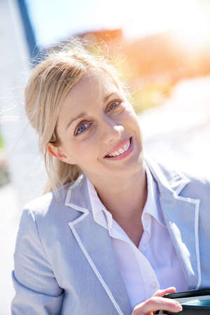 woman business suit: Portrait of smiling businesswoman standing outside