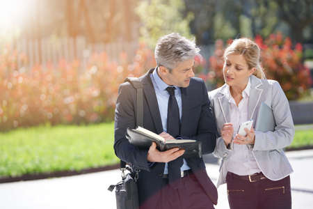 woman business suit: Business partners meeting outside and sharing schedule availabilities