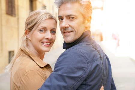 mujeres felices: pareja caminando de mediana edad en la calle del casco antiguo español