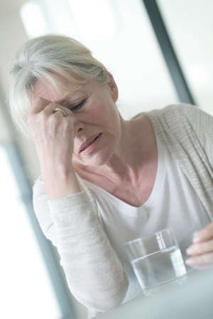 ailing: Senior woman suffering migraine