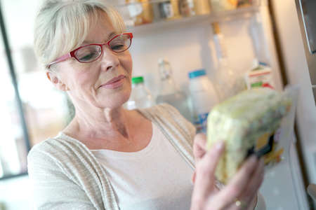 Senior woman checking expiration date on food product