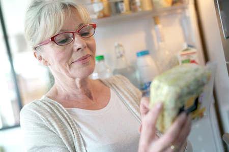 Ltere Frau überprüft Ablaufdatum auf Lebensmittelprodukt Standard-Bild - 76362106