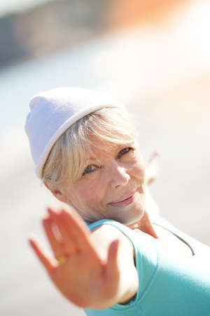 exercices: Senior blond woman doing yoga exercices on the beach