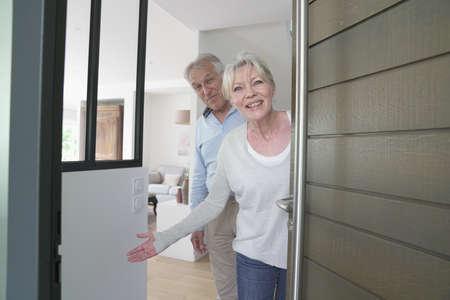 Les personnes âgées accueillent les amis pour entrer dans la maison